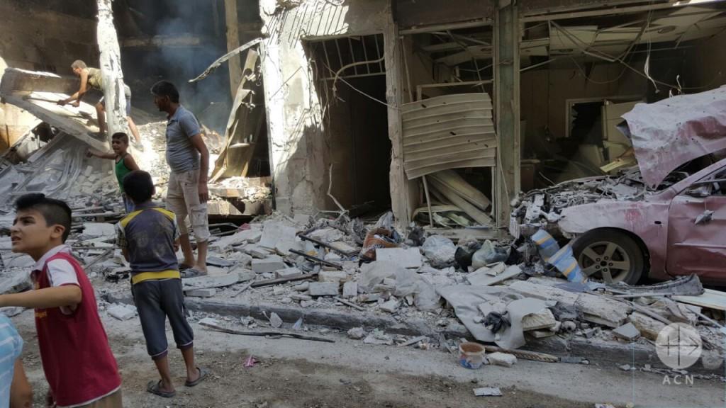 Alep, Syrie, 11 juillet 2016. Des enfants regardent les dommages causés par des bombardements.